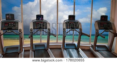 Image of treadmills in fitness club with view of the beach