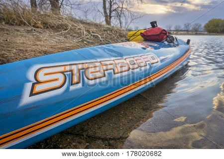 FORT COLLINS, CO - March 21, 2017:  All Star racing stand up paddleboard by Starboard with waterproof case and bag on a deck, early spring lake scenery.