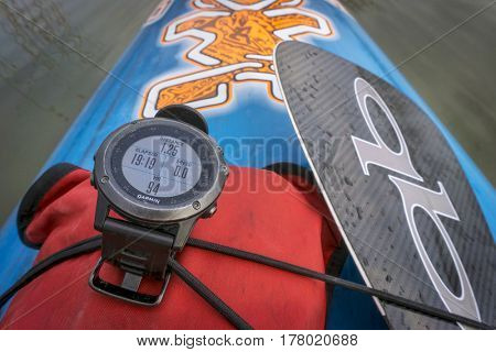 FORT COLLINS, CO - March 21, 2017:  A well used Garmin multisport GPS Fenix 3 watch on a deck of stand up paddleboard by Starboard with a dry bag and Quickblades carbon paddle.