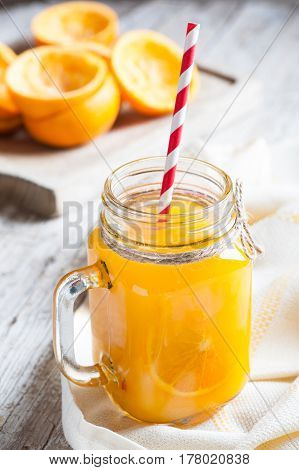 Orange juice in glass on old wooden table