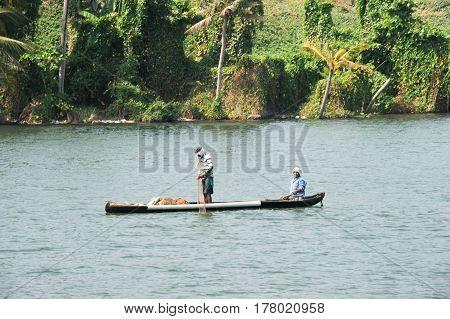 Kollam India - 20 January 2015: Fisherman fishing on a canoe near Kollam on Kerala backwaters India