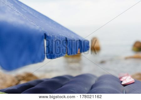 Rain raindrops flow down the beach umbrella which stands on the beach overlooking the sea and rocks. Near the inflatable mattress on which lie pink children's flip flops. Summer the sea.