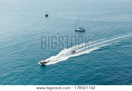 The motor boat sails on the black sea and carries on people's inflatable banana in life jackets. In the background are two sailing yachts. Horizontal shot summer rest daylight.