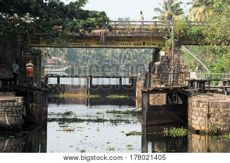 Kollam India - 20 January 2015: People opening the gate for a boat passing a barrage on the way from Kollam to Alleppey on Kerala India