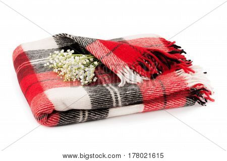 Checkered warm blanket and a bouquet lilies of the valley isolated on white background.