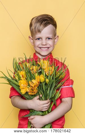 Little beautiful child with pink shirt gives a bouquet of tulips on Women's Day, Mother's Day. Birthday. Valentine's day. Spring. Studio portrait over yellow background