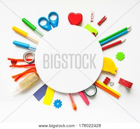 Round frame with stationery on the white background. Multicolor pencils and crayons. Place for your text.