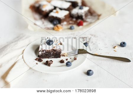 Table setting chocolate dessert brownie cake with berries on a white plate on a table covered with a linen tablecloth. The second part of the cake on the parchment paper. Horizontal image daylight.