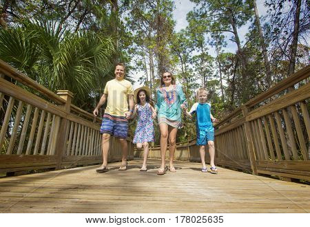 Happy young family having fun together while on a tropical island vacation.