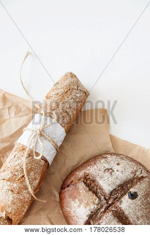 Cooking of homemade bread black round bread and baguette lie on parchment paper on a white background. Space for text daylight.