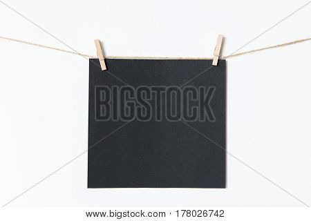 Black sheet for applying text is attached by wooden clothespins on a white background. Write your text.