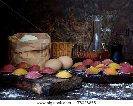 Raw Pink Yellow Beet Dumplings Or Ravioli Stuffed With Ricotta Cheese On Wooden Board On Dark Backgr