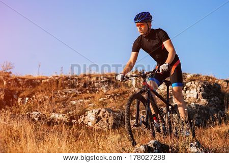 Professional Cyclist Riding the Bike at the Rocky Trail. Sportsman in the helmet and sunglasses. Cyclist in the sportwear. Extreme Sport Concept. Free Space for Text. Travel in the countryside. Spring season.