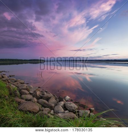 Pink sunset on the lake. Evening blue sky reflected in the water. Camping near the lake