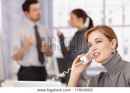 Giovane imprenditrice parlando sul telefono in ufficio, i colleghi in chat in background.?