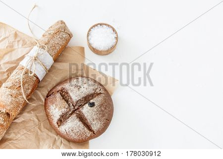 Cooking of homemade bread black round bread and baguette lie on parchment paper on a white background with salt. Space for text daylight.