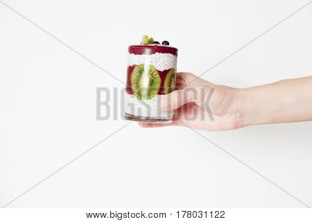Smoothies in a glass in a hand on a white background with berries and fruits blueberries kiwi and chia seeds. Horizontal image daylight space for text.