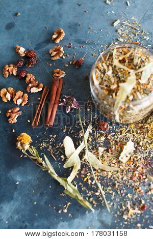 Cinnamon sticks nuts and a herb collection scattered on a blue table a glass jar with tea lime mint lemon balm chamomile. Daylight vertical image.