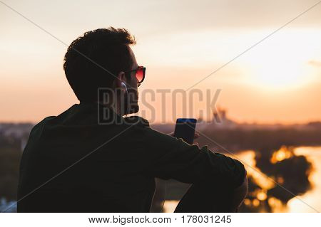 Young man enjoying sunset listening to the music on the smartphone