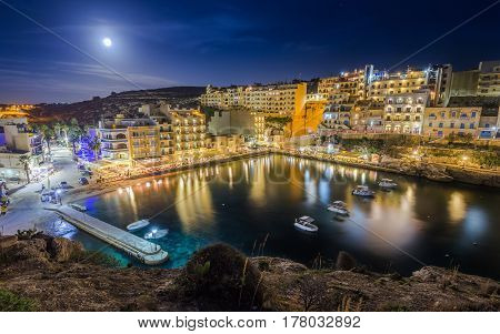 Xlendi Gozo - Night photograph of Malta's most beautiful mediterranean town with busy night life restaurants hotels and moon light on the island of Gozo