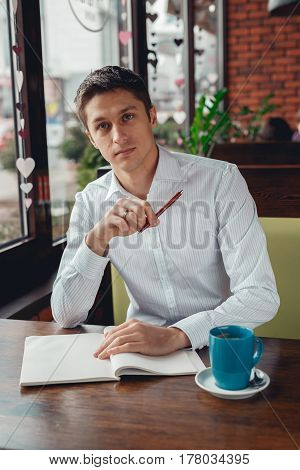 Man with notebook and cup of coffee writing something.