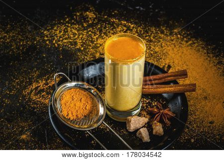 Traditional Indian drink turmeric milk is golden milk with cinnamon cloves pepper and turmeric. On a concrete table with spices on the background. In glass on black plate Horizontal toned copy space