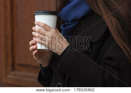 Young Woman Hands With Coffee Disposable Cup Outdoors With Wooden Doors Background