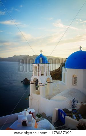 traditional greek village Oia of Santorini, with blue domes of churches at sunset, Greece, retro toned