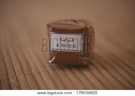 Ground cinnamon texture. Cinnamon on wooden background. Healthy food. Cinnamon powder background. Closeup view of cinnamon package. Spices of the world.