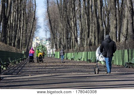 people men women girls with baby strollers walking along the path in the Park spring Sunny day Petersbugr Russia summer garden season