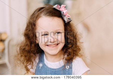 Laughing girl with curly hair in studio