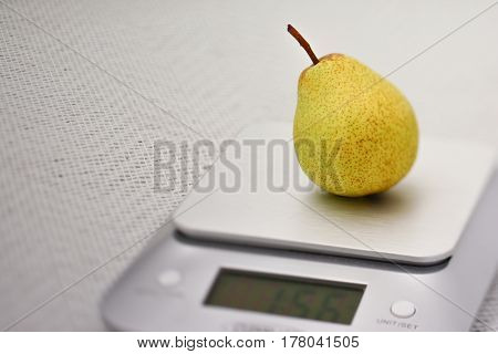 Single Williams pear on a kitchen scale