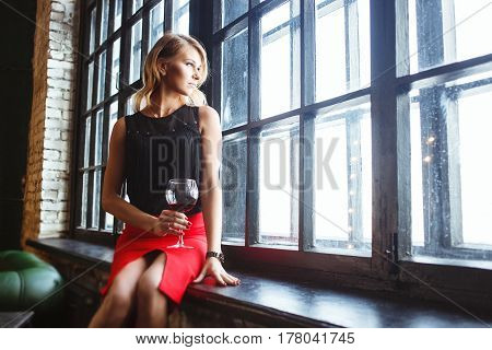 Luxury woman in red skirt with glass of wine looking through window