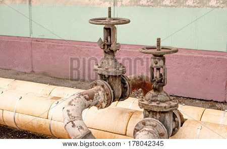 Two old rusty hot water valves onpipes outdoors