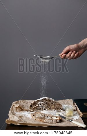 Woman Sieving Flour onto Loaf of Walnut Bread on Table
