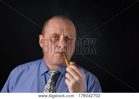 Nice portrait of mature office clerk smocking tobacco pipe against black background