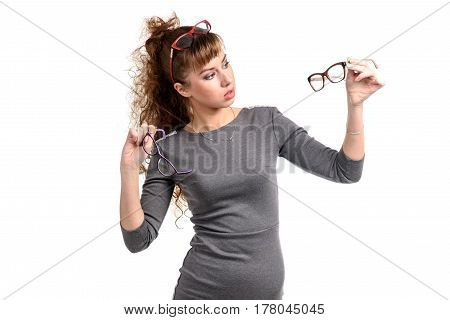 Pretty thoughtful woman standing with the glasses isolated on white.
