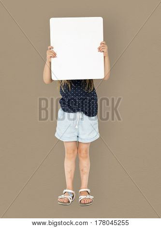 Little girl smiling and holding blank placard cover her face