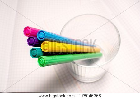 Felt Tip Pens In A Cup On A Checkered Notebook