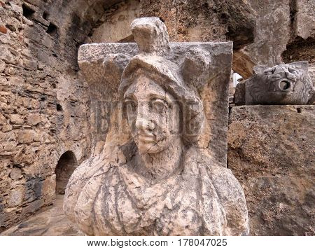 Ancient statue of a brown stone on the ruins of the ancient city of Side