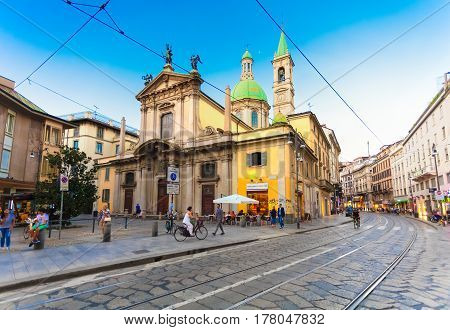 MILAN ITALY - September 07 2016: View on the Saint George Church (Chiesa San Giorgio al Palazzo) people and cobbled Torino street with rails for Milan tram in the evening.