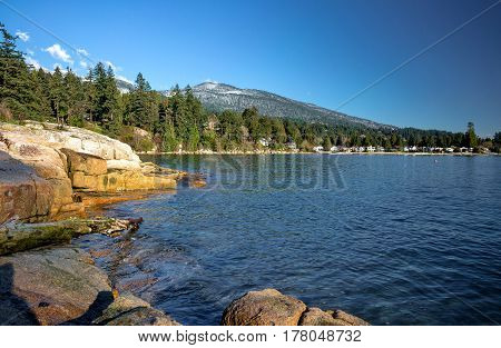 A village on a rocky beach in the  Strait of Georgia British Columbia, a coastline and a forest in the background of a mountain view