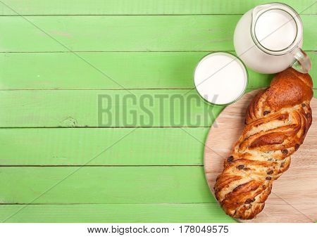 jug of milk with a loaf of bread on a green wooden background with copy space for your text. Top view.