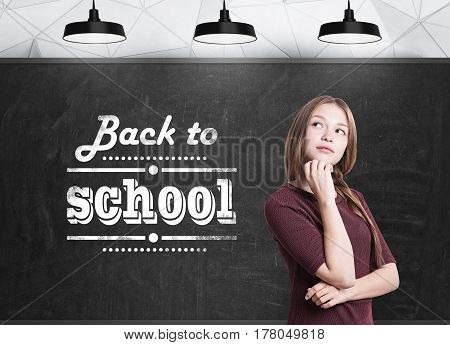 Portait of a young woman with braided hair standing near a blackboard with a back to school text written on it.