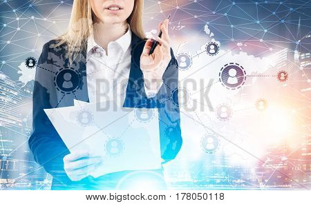Close up of businesswoman with papers standing against a city panorama and a network sketch in the sky. Toned image double exposure.