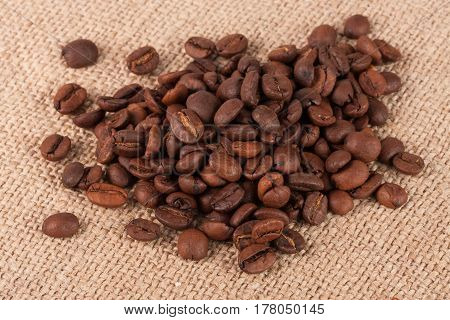 pile of coffee beans on sackcloth close up macro.