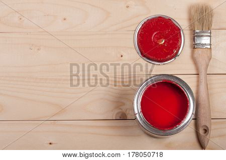 red paint in the bank to repair and paint brush on the light wooden background with copy space for your text. Top view.