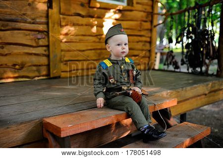 Child in military uniform with a toy gun on the background of a wooden house