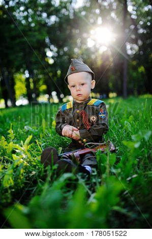 The child in military uniform with a ribbon of siege sits in the grass against the sunset. May 9, Victory Day, February 23,