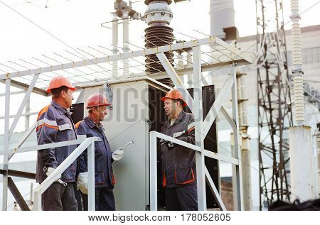 Three electrical engineers discuss the equipment repair plan. Power station